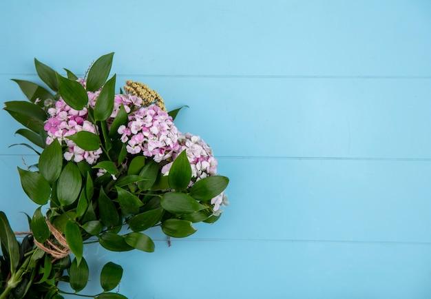 Vista superior do buquê de flores roxas claras com ramos de folhas em uma superfície azul clara