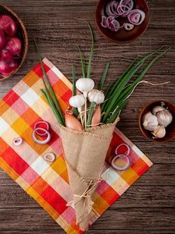 Vista superior do buquê de legumes como cebola cebola e alho no pano em fundo de madeira