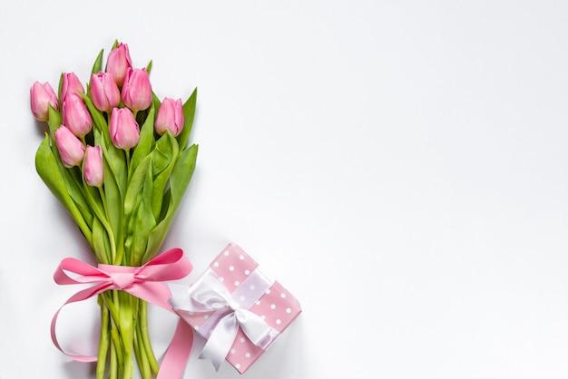Vista superior do buquê de tulipas cor de rosa, envolvida com fita rosa e caixa de presente pontilhada rosa sobre fundo branco. copie o espaço.
