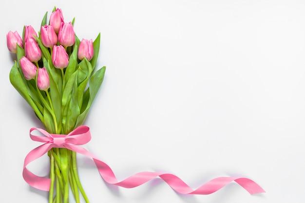 Vista superior do buquê de tulipas cor de rosa, envolvida com fita rosa em fundo branco. copie o espaço.