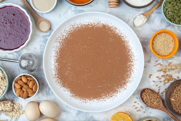 Vista superior do cacau em pó em tigelas de prato redondo com geléia, amêndoas, aveia, sementes de gergelim, trigo, grãos, ovos, mesa