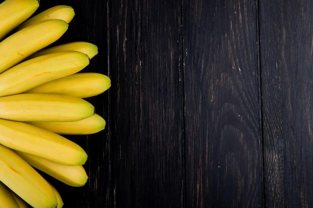 Vista superior do cacho de bananas em madeira rústica, com espaço de cópia