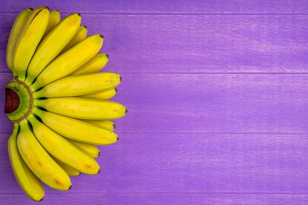 Vista superior do cacho de bananas, isolado na madeira roxa, com espaço de cópia