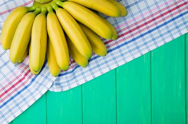 Vista superior do cacho de bananas, isolado na madeira verde, com espaço de cópia