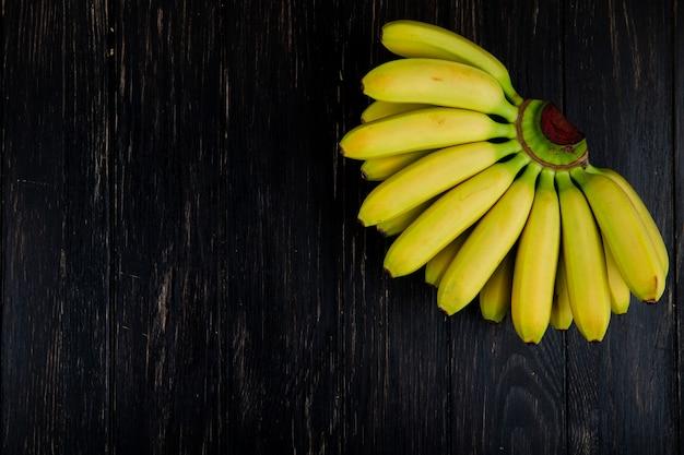 Vista superior do cacho de bananas na madeira preta com espaço de cópia