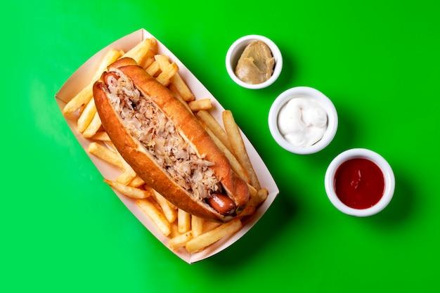 Vista superior do cachorro-quente com atum servido com batatas fritas maionese ketchup e mostarda