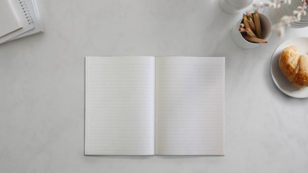 Vista superior do caderno aberto no espaço de trabalho simples com artigos de papelaria e croissant na mesa de mármore