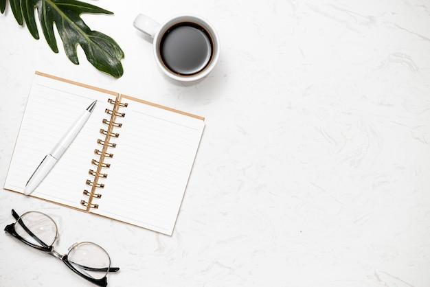 Vista superior do caderno aberto para anotações, caneta, copos e xícara de café sobre fundo de mármore branco.