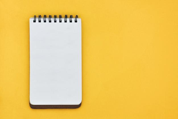 Vista superior do caderno aberto vazio em amarelo