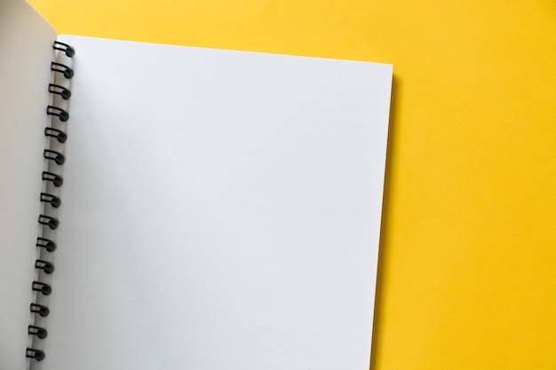 Vista superior do caderno aberto vazio no fundo preto amarelo com espaço de cópia, plano plano