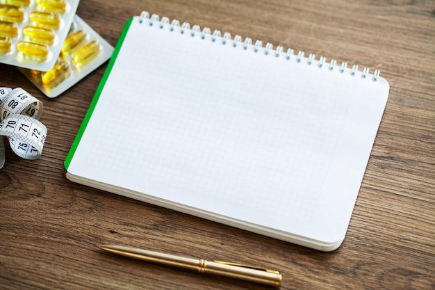 Vista superior do caderno branco na mesa de madeira.