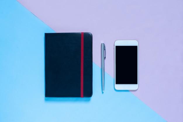 Vista superior do caderno, caneta em azul e rosa pastel cor bakcground