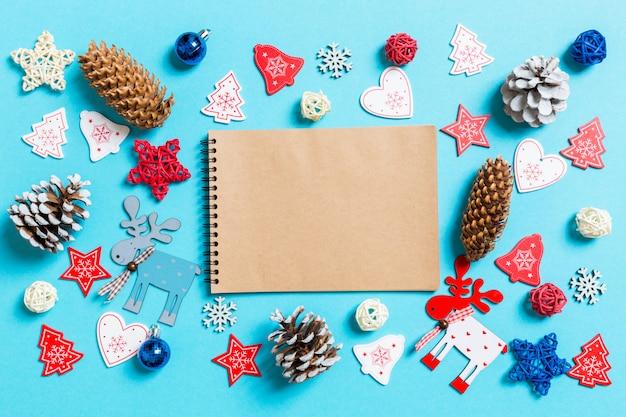Vista superior do caderno cercada com brinquedos de natal e decorações em fundo azul. conceito de tempo de natal