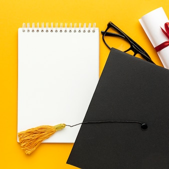 Vista superior do caderno com boné acadêmico e óculos
