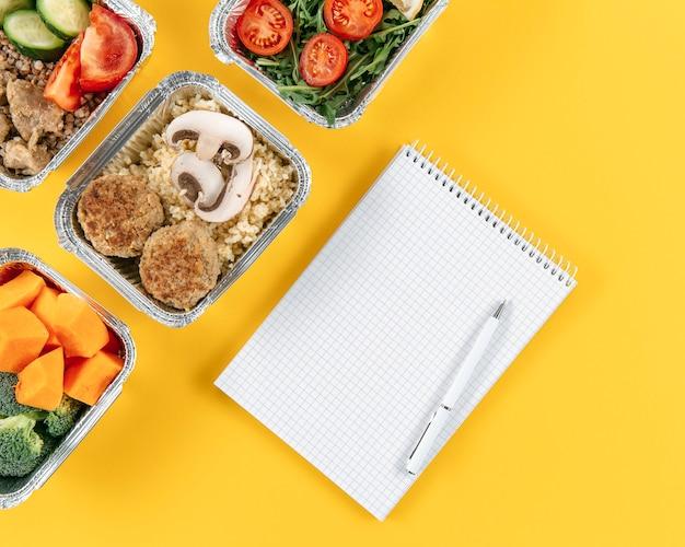 Vista superior do caderno com caneta e refeições em caçarolas