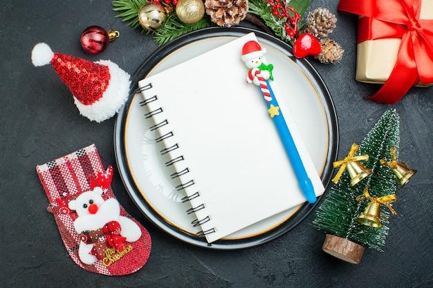Vista superior do caderno com caneta no prato de jantar árvore de natal ramos de coníferas cone caixa de presente chapéu de papai noel meia de natal em fundo preto