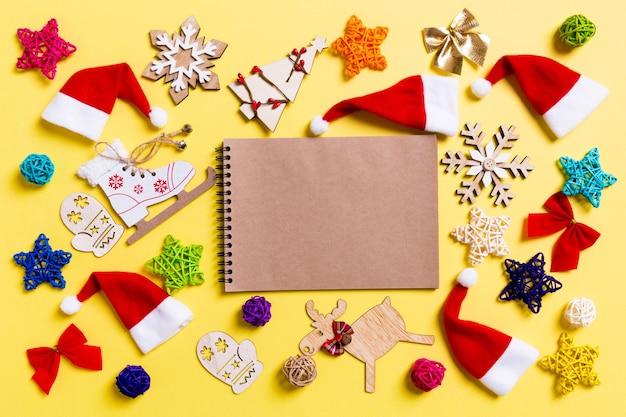 Vista superior do caderno com decorações de natal e chapéus de papai noel em fundo amarelo. conceito de férias felizes.