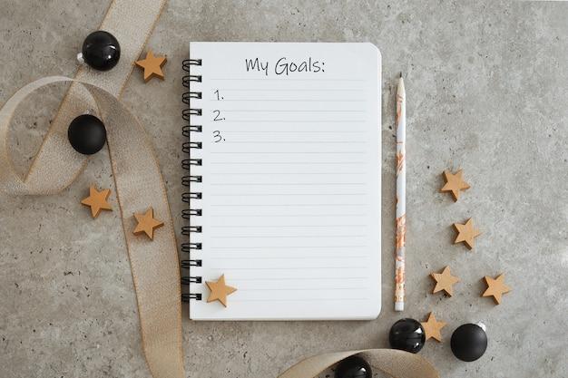Vista superior do caderno com decorações de natal. lista de metas para o ano novo. espaço livre, copie o espaço, maquete ou modelo para o seu texto.