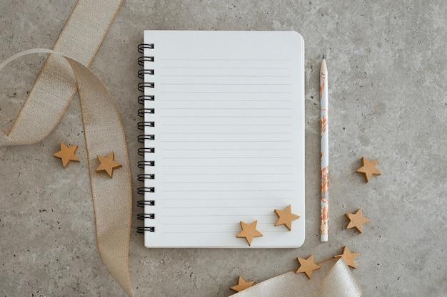 Vista superior do caderno com decorações de natal. metas, planos, sonhos e lista de afazeres para o ano novo. espaço livre, copie o espaço, maquete ou modelo para o seu texto.