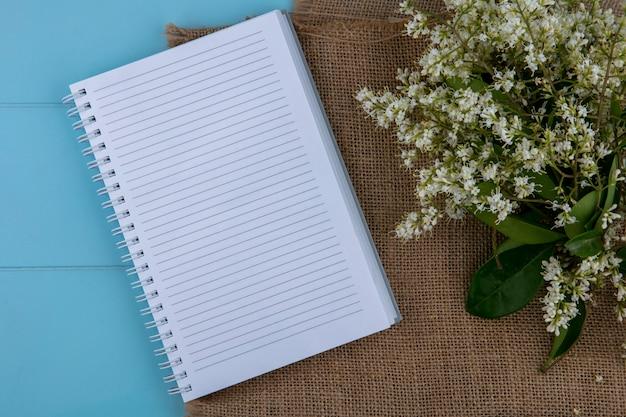 Vista superior do caderno com flores em um guardanapo marrom