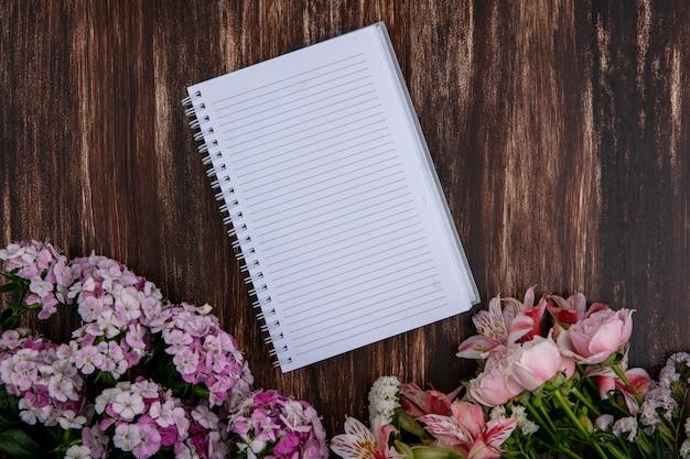 Vista superior do caderno com flores rosa claro, lírios e rosas em uma superfície de madeira