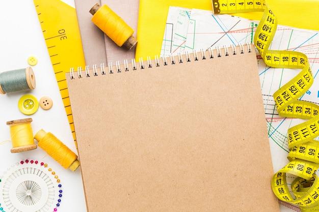 Vista superior do caderno com tecidos e fita métrica