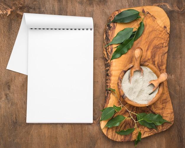 Vista superior do caderno com tigela de pó e colheres