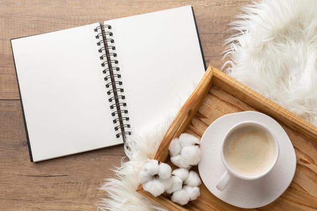 Vista superior do caderno com xícara de café e flores de algodão