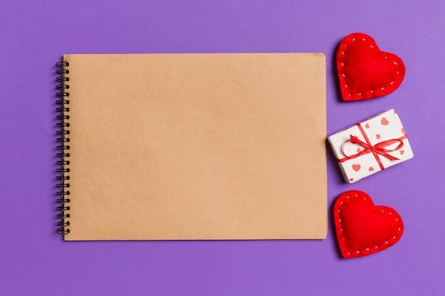 Vista superior do caderno de artesanato cercado com caixa de presente e corações