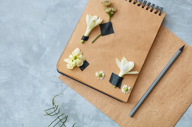 Vista superior do caderno de artesanato com decoração de flores e lápis no fundo de concreto, vista aérea