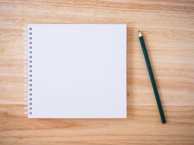 Vista superior do caderno de capa branca em branco com lápis na mesa de madeira marrom