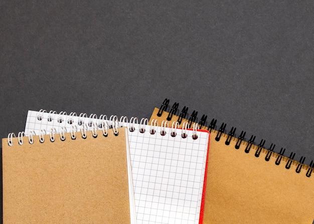 Vista superior do caderno de capa preta fechado com lápis no fundo branco da mesa