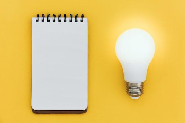 Vista superior do caderno de linhas abertas vazio e lâmpada led no conceito de ideias de fundo amarelo