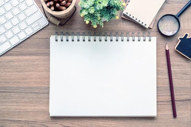 Vista superior do caderno de página em branco com suprimentos na mesa de madeira.