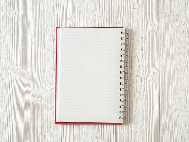 Vista superior do caderno de papel em fundo branco de madeira