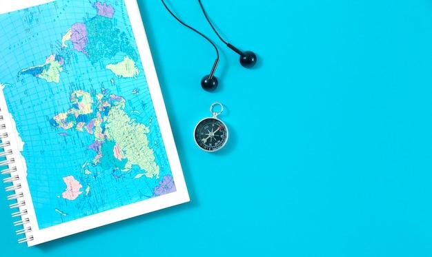 Vista superior do caderno de viagem com mapa-múndi, bússola magnética e fones de ouvido em azul. postura plana