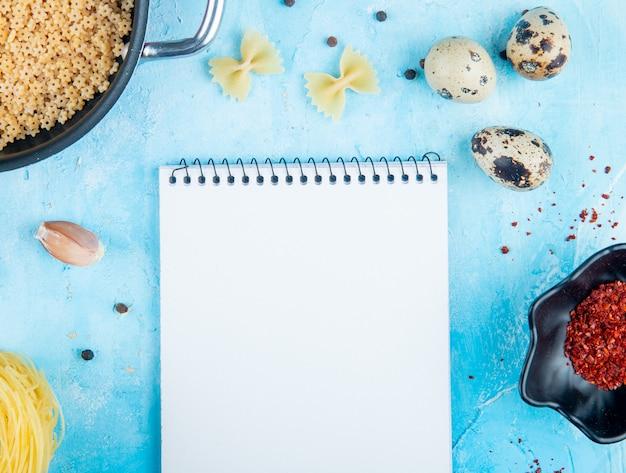 Vista superior do caderno e macarrão farfalle cru ovos de codorna pequenos em forma de estrela macarrão em uma tigela e flocos de pimenta vermelha em um pires em fundo azul