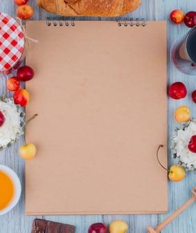 Vista superior do caderno e queijo cottage com cerejas frescas de amarelas e vermelhas maduras, dispostas em cinza