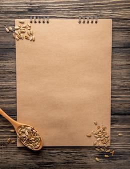 Vista superior do caderno e uma colher de pau com sementes de girassol no rústico