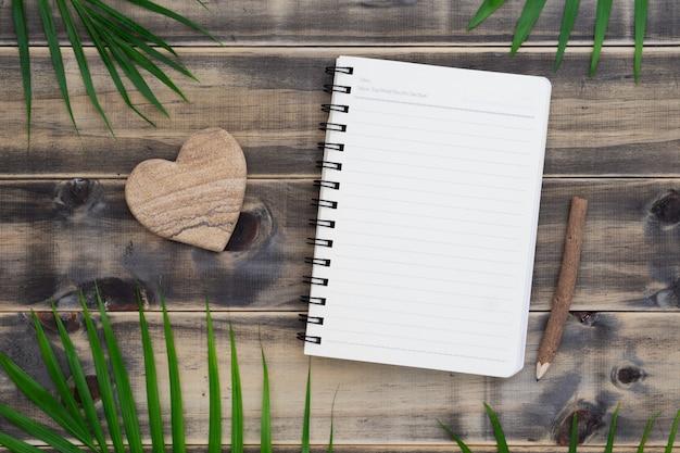 Vista superior do caderno em branco com folha de palmeira e coração forma pedra na madeira