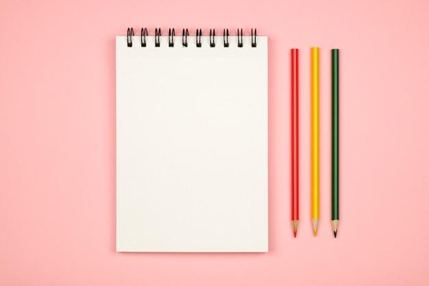 Vista superior do caderno em branco com lápis de cor