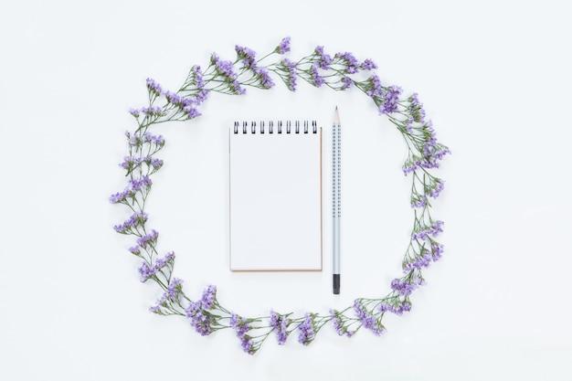 Vista superior do caderno em branco com lápis no quadro floral da flor