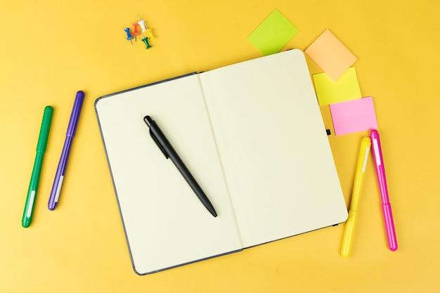 Vista superior do caderno em branco e material escolar, como marcadores coloridos, adesivos e clipers em fundo amarelo, espaço para texto.