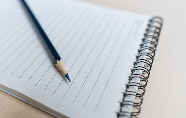 Vista superior do caderno em branco espiral aberta com lápis sobre fundo marrom