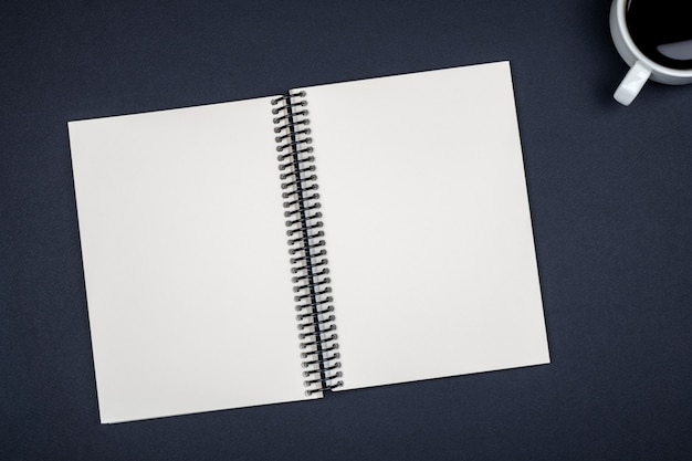 Vista superior do caderno em branco espiral aberta na mesa colorida