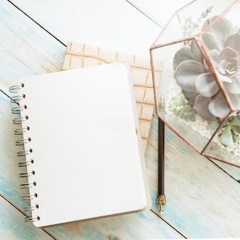 Vista superior do caderno espiral branco vazio em uma mesa limpa com plantas suculentas em um vaso e lápis