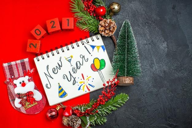 Vista superior do caderno espiral com a escrita de ano novo e os acessórios de decoração de desenhos ramos de abeto xsmas números de meias em um guardanapo vermelho e a árvore de natal no lado direito em fundo escuro