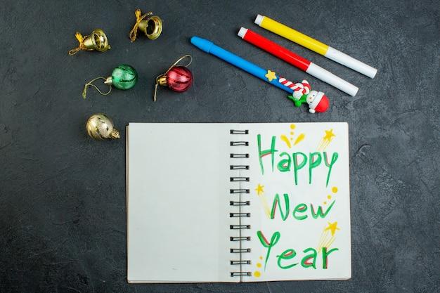 Vista superior do caderno espiral com acessórios de decoração de escrita de feliz ano novo em fundo preto