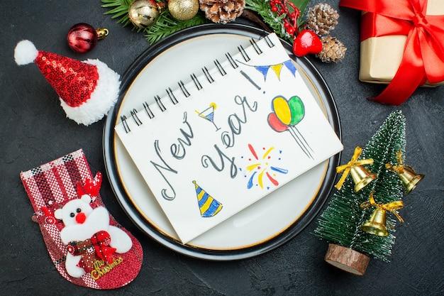 Vista superior do caderno espiral com caneta no prato de jantar árvore de natal ramos de coníferas cone caixa de presente chapéu de papai noel meia de natal em fundo preto