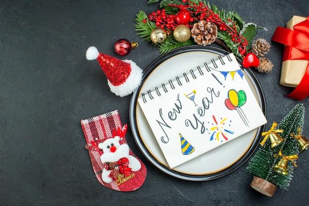 Vista superior do caderno espiral com caneta no prato de jantar árvore de natal ramos de coníferas cone caixa de presente chapéu de papai noel meia de natal no lado esquerdo em fundo preto